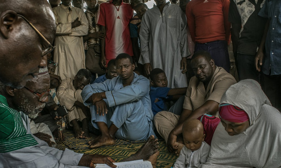 Zalika Amadou signing forms to divorce her husband, center, at a street-side court in Maradi, Niger.  (Laura Boushna for The New York Times)